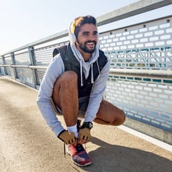 Supports Healthy pH Balance – Man along a bridge tying his shoe to prepare for a run