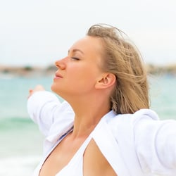 Safe & Non-Toxic – Woman in white on the beach with her eyes closed and arms stretched out to the sides