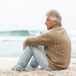 All-Natural Formula – Man sitting on sand enjoying the view of the waters