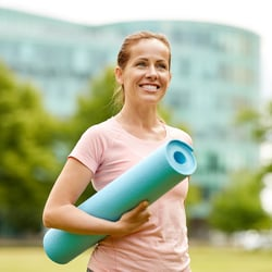 Boost Your Well-Being – Woman standing in park with yoga mat