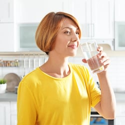Don't Risk Low Selenium – Woman drinking a glass of water in a white kitchen
