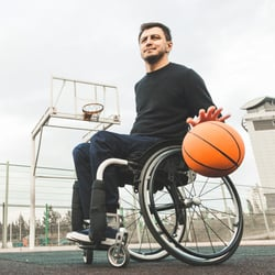 Helps Heart Health - Man in wheelchair dribbling a basketball on the basketball court