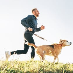 Stay Energized – Man jogging with dog alongside
