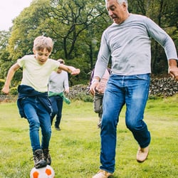 Supports Bone Health – Father and son playing soccer in the backyard