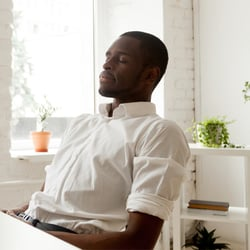 Prepare Your Mind – Man resting in office leaning back in chair with his eyes closed.