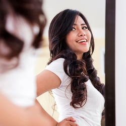 Fasting & Weight Loss – Woman smiling in front of a mirror.