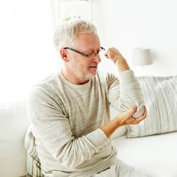 Soothes Redness & Swelling – Middle-aged man sitting on couch holding one of his elbows