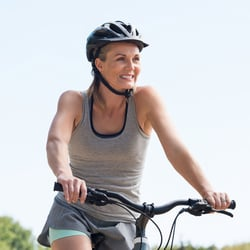 Middle-aged woman wearing a helmet on a bicycle