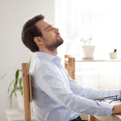Balances Mental Well-Being – Man leaning slightly back in his chair and resting with his eyes closed