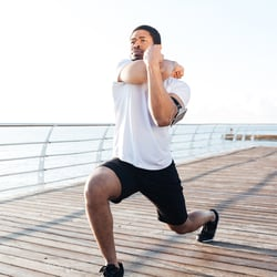 Eases Tense Muscles – Man stretching on a boardwalk