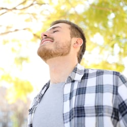 Give Your Immune System a Boost – Man standing under trees and enjoying the sun