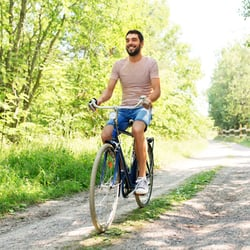 Revitalizes Energy Levels – Young man riding bicycle along a park trail