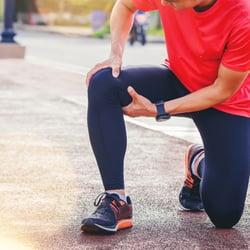 Quickens Healing – Man stretching his leg on a sidewalk